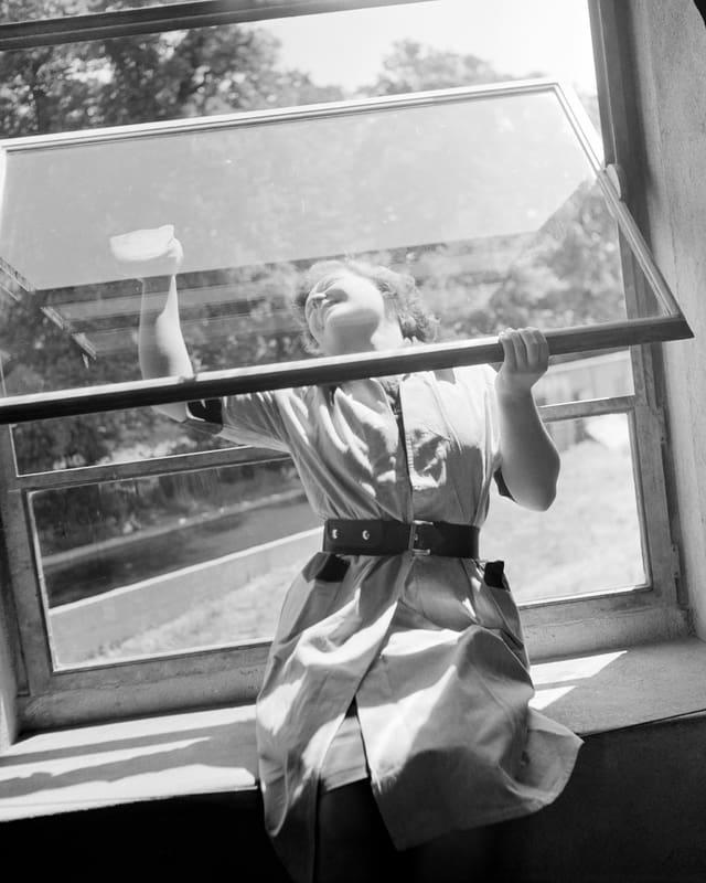 Eine Frau beim Fensterputzen.