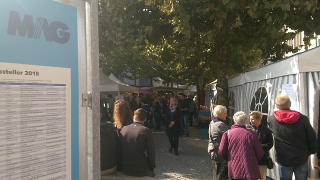 Ein Schild. Daneben verschiedene Stände einer Herbstmesse.