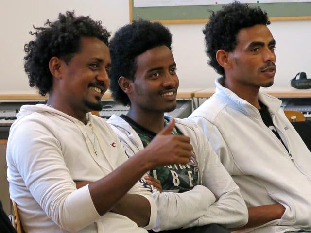 Drei Männer aus Eritrea sitzen nebeneinander und lachen.