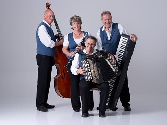 Eine Musikformation mit einer Musikantin und drei Musikanten, die mit Bassgeige, Klarinette, Akkordeon und Piano fürs Gruppenbild posieren.