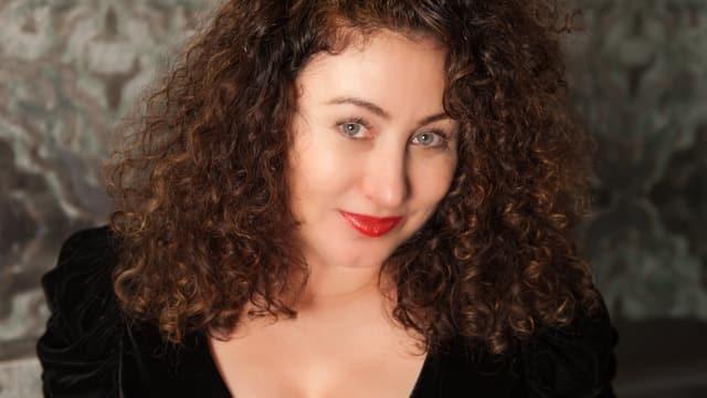 Kopf einer Frau mit lockigen, offenen Haaren.