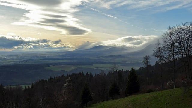 Blick über Wiesen und Wald auf Ebene und Berge mit blauem Himmel und Wolken.