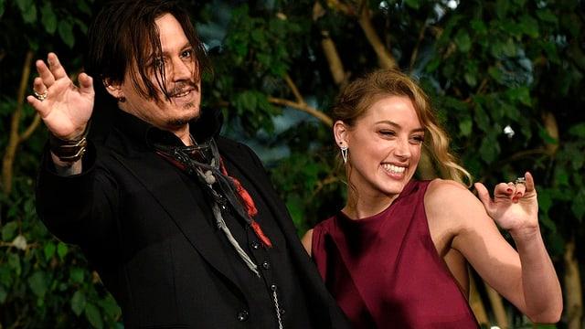 Johnny Depp und Amber Heard winken in die Kameras.