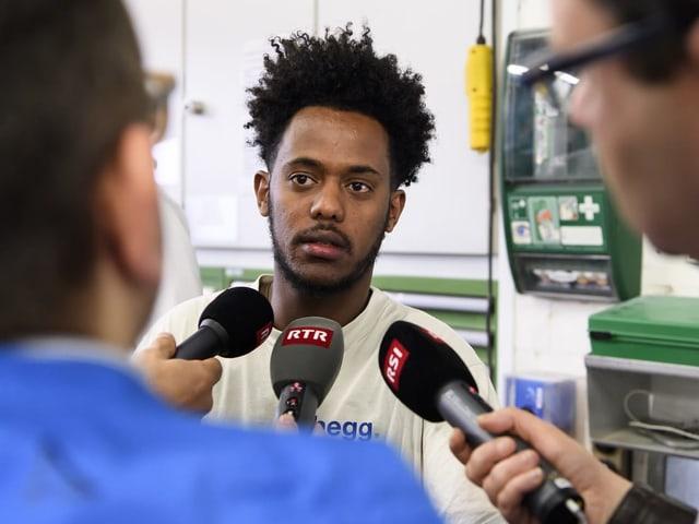 Solomon Aklilu è circumdà da schurnalists che vulan savair dapli da sia lavur.