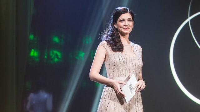 Eine Frau im Abendkleid auf einer Bühne beim Moderieren einer Show.