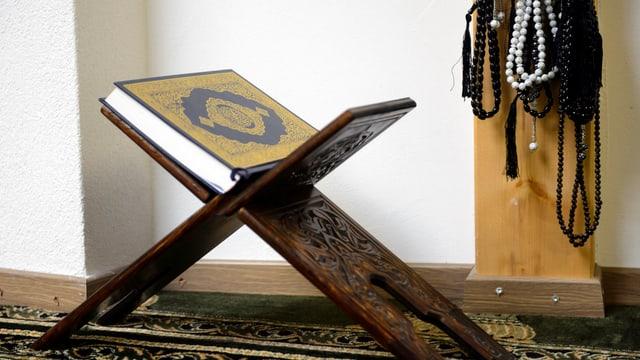 arabischer Schemel mit Koran darauf, daneben aufgehängt Betkränze