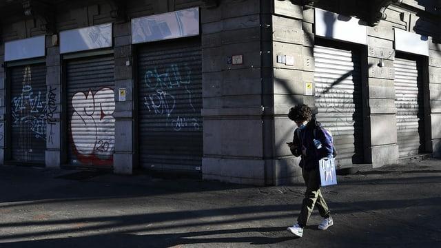 Eine Person läuft in Mailand an einem geschlossenen Geschäft vorüber.