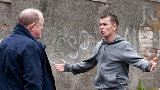 Ein junger Mann mit Kapuzenpulli streckt seine Arme seitlich in die Luft und redet auf einen älteren Mann ein.