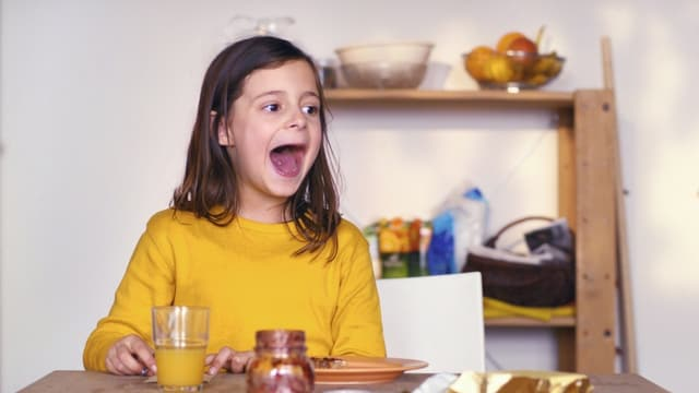 Ein Mädchen sitzt am Frühstückstisch.
