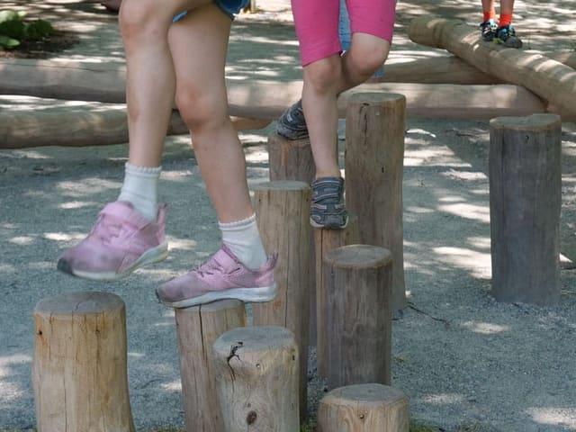 Kinder laufen über Holzpflöcke