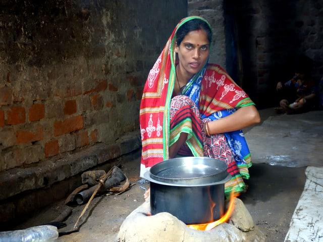 Eien Frau sitzt hinter einem Kochtopf, der über einem Feuer am Boden steht.