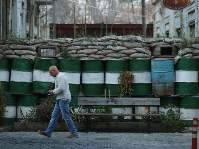 Mann geht an Pufferzone aus Öltonnen und Sandsäcken vorbei