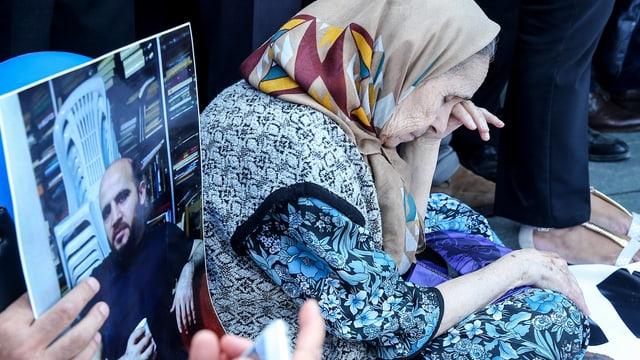 Eine ältere Frau sitzt bedrückt am Boden. Neben ihr hält jemand ein Foto von Ahmed Sik in die Kamera.