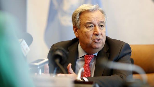 Guterres sitzt vor einer UNO-Flagge an einem Tisch und spricht in ein Mikrofon.