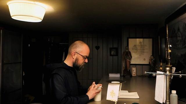 Ein Mönch betet an einem Tisch.