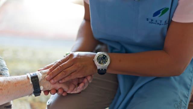 Spitex-Mitarbeiterin im blauen Übergewand fühlt einer älteren Frau den Puls