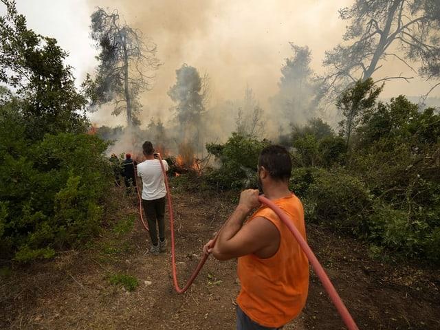 Gli uomini hanno una manichetta antincendio.  I vigili del fuoco sono alla fine del tubo.