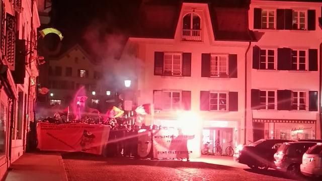 Demonstranten mit roten Fackeln in Stadt.