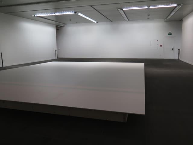 Eine leere, weisse Bühne in einem Raum.
