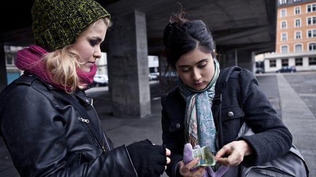 Zwei Mädchen stehen unter einer Brücke, eines gibt dem anderen Geld.