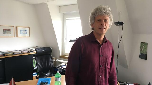 Porträt von Kreisschulpflege-Präsident Urs Berger in seinem Büro. Weisse Haare, rotes Hemd.