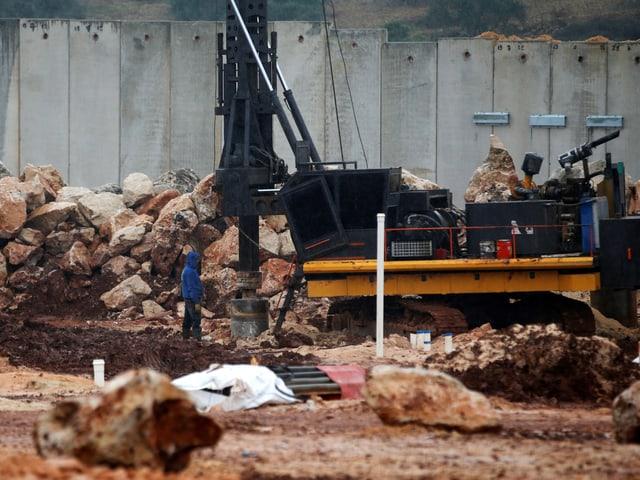 Mann steht neben Maschine, die ein Loch zum Tunnel bohrt