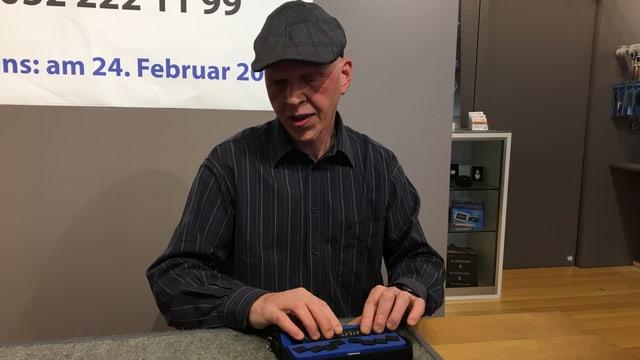 Stefan Hofmann sitzt vor der Braille-Tastatur