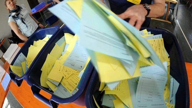 unzählige Wahlzettel in blauen Plastikboxen