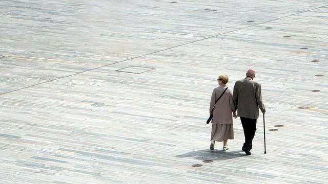 Ein älteres Paar läuft über einen Platz