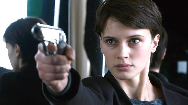 Eine Frau mit gezückter Waffe. Im Spiegel sieht man ihren Hinterkopf.