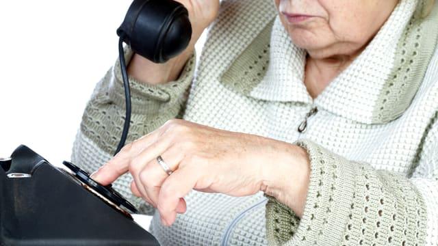 Alte Frau an einem alten Telefon