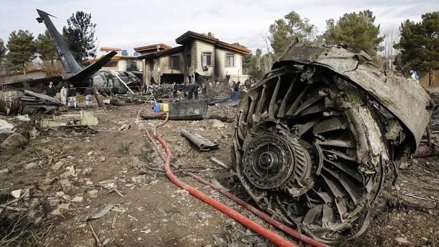 Flugzeugwrack und beschädigte Häuser