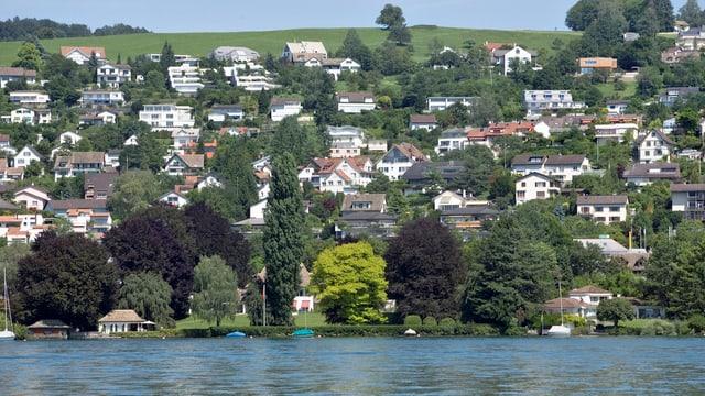 Viele Häuser, zwischendurch Bäume, vorne See