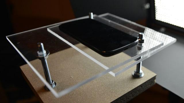 Smartphone auf einem Gestell mit Plexisglas