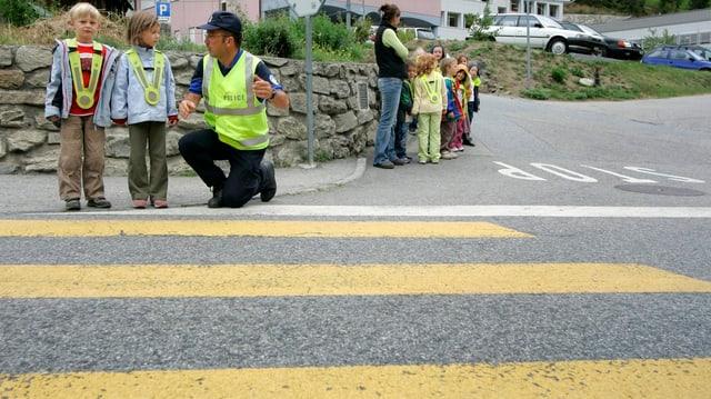 Polizist mit Kindern vor einem Fussgängerstreifen.