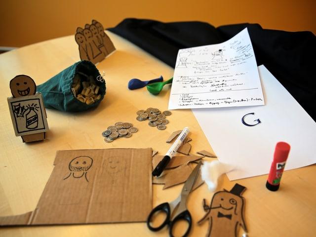 Pappmännchen, Kleingeld, Scrabble-Steine und Bastelmaterial liegen auf einem Bürotisch.