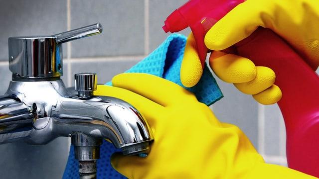 Zwei Hände in gelben Gummihandschuhen mit Putzmittel und Lumpen beim Reinigen einer Badewannenarmatur.