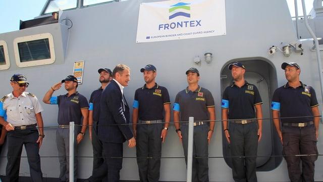 Grenzschutzbeamte der Frontex aufgereiht vor einer Wand.