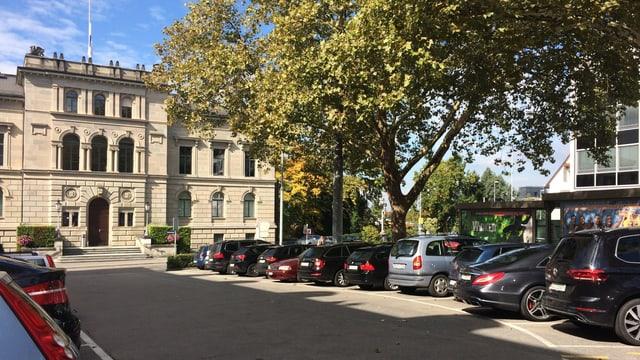 Ein Gebäude aus Stein, davor ein Parkplatz.