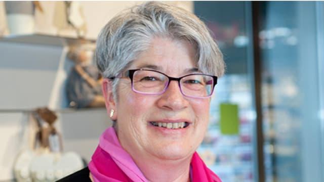 Helene Hutterli mit Brille und rosa-rotem Schal in einem Geschäft.