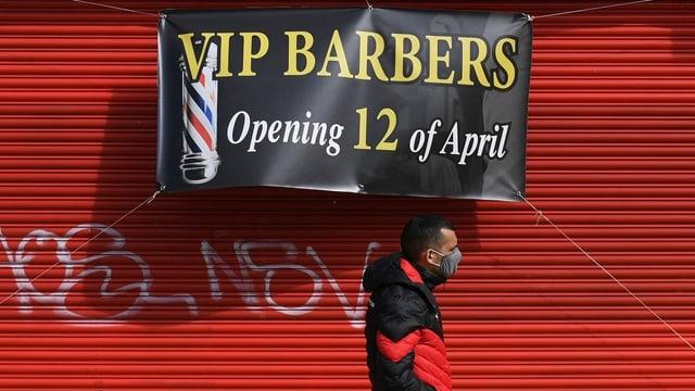 Eine Person mit Maske geht an einem Plakat vorbei, das ankündigt, dass ab Montag ein Friseur wieder öffnet.