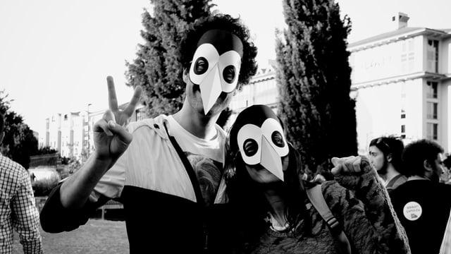 Junge Menschen mit Vogelmasken.