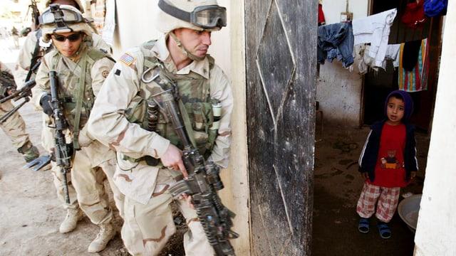 US-Soldaten dringen in ein Haus ein. Am Eingang steht ein kleiner Junge.