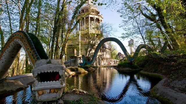 Kunstwerke von Bruno Weber - eine Schlange und ein Haus. Dazwischen ist ein Weiher.