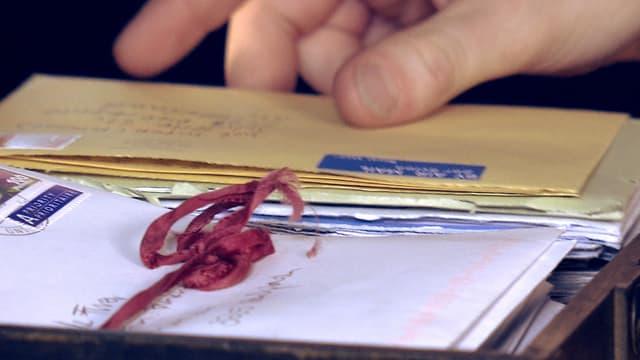 Jael nimmt ein Briefcouvert in die Hand.