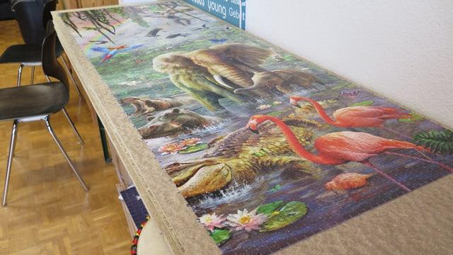 Fertige Tranche des Puzzles mit einem Elefanten und Flamingos.