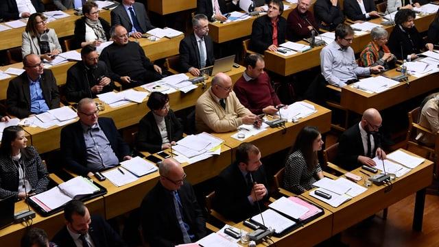 Blick auf Parlamentarier die an kleinen Tischchen sitzen.
