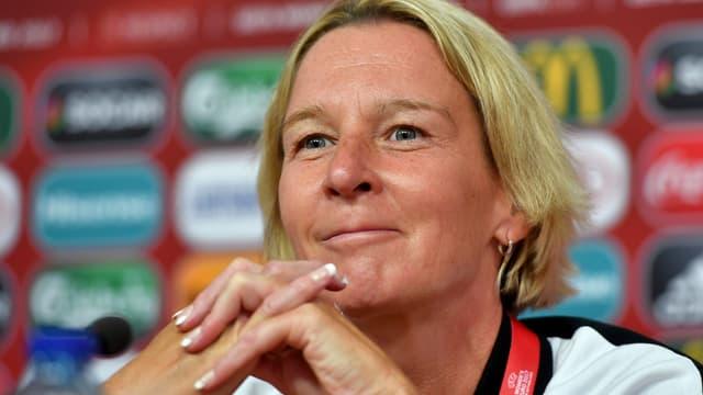 Martina Voss-Tecklenburg bei einer Medienkonferenz mit gefaltete Händen.