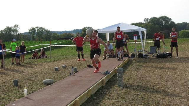 Ein Athlet hat den Stein wie die Kugel beim Kugelstossen und rennt.