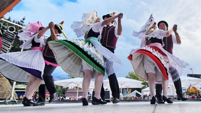Drei Paare in traditionellen Trachten tanzen auf einer Bühne.